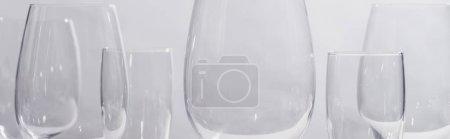 Panoramic shot of shiny glasses isolated on grey