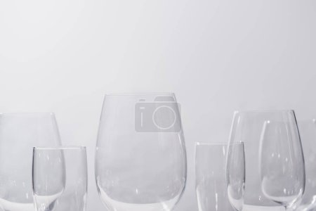 Empty champagne and wine glasses isolated on grey