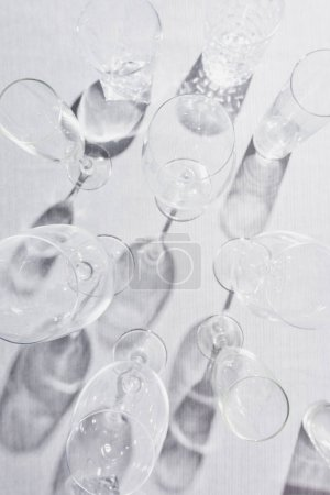 Photo for Top view of transparent glasses with shadow on grey cloth - Royalty Free Image