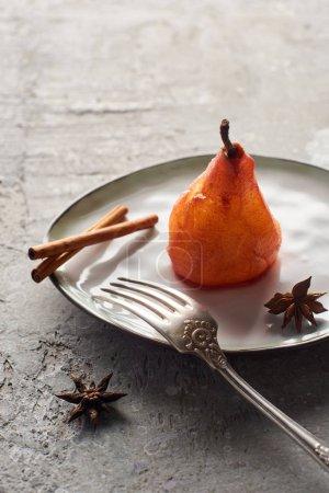 delicioso pera en vino con canela y anís en plato con tenedor de plata en la superficie de hormigón gris