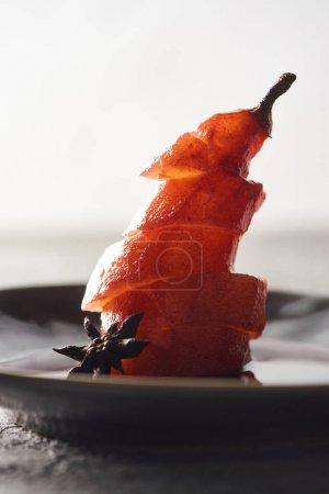 Photo pour Vue rapprochée de délicieuses tranches de poire dans le vin avec de l'anis sur l'assiette - image libre de droit