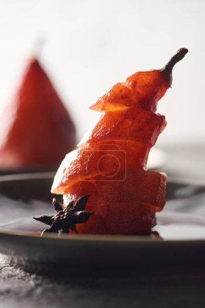 Nahaufnahme von köstlichen Birnenscheiben in Wein mit Anis auf dem Teller