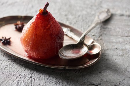 Photo for Delicious pear in wine with anise on plate with silver spoons on grey concrete surface - Royalty Free Image