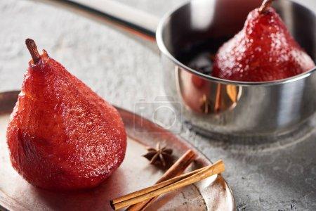 selektiver Fokus von köstlicher Birne im Wein in der Pfanne und auf Silberteller mit Zimt und Anis auf grauer Betonoberfläche