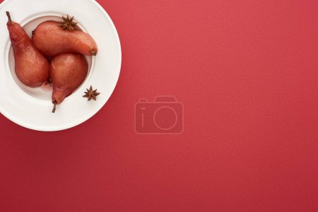Photo for Top view of delicious pear in wine with anise on plate on red background - Royalty Free Image