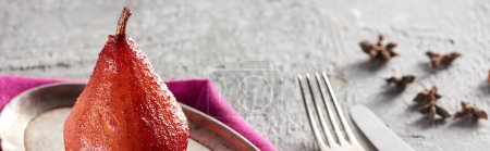 delicious pear in wine with anise on silver plate on grey concrete surface with pink napkin, knife and fork, panoramic shot
