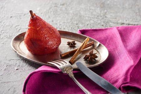 köstliche Birne in Wein mit Zimt und Anis auf Silberteller auf grauer Betonoberfläche mit rosa Serviette, Messer und Gabel