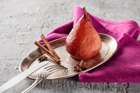 delicious pear in wine with cinnamon and anise on silver plate on grey concrete surface with pink napkin, knife and fork