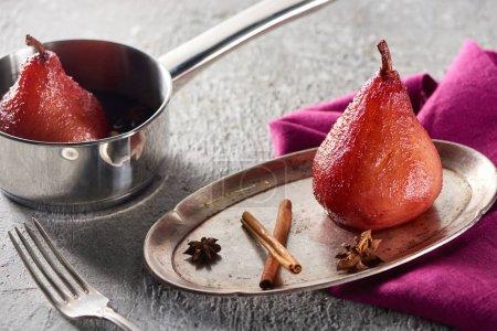 Photo pour Délicieuse poire dans le vin à la cannelle et à l'anis sur plaque argentée et en pot sur une surface en béton gris avec serviette rose et fourchette - image libre de droit