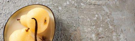 Photo pour Vue de dessus de délicieuse poire dans le vin servi avec des épices sur plaque sur la surface en béton gris, vue panoramique - image libre de droit