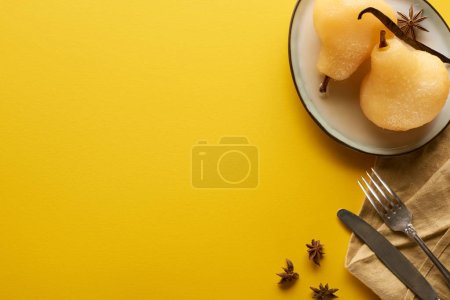 Photo for Top view of delicious pear in wine with anise on plate near cutlery and napkin on yellow background - Royalty Free Image