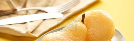 selective focus of delicious pear in wine on plate near napkin and cutlery, panoramic shot
