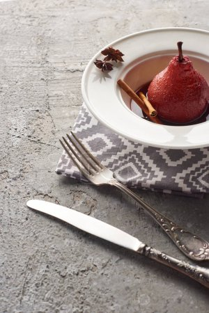 delicious pear in red wine with cinnamon and anise on plate on grey concrete surface with cutlery on napkin