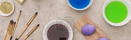 Foto de Vista superior de los huevos de pollo, brillo y pinturas a acuarela con pinceles en la superficie gris de hormigón, tiro panorámico. - Imagen libre de derechos