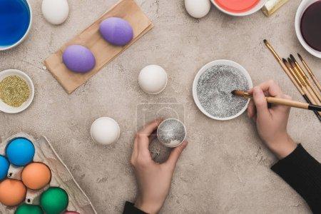 Photo pour Vue recadrée d'une femme décorant des œufs de poulet avec des paillettes argentées sur une surface en béton gris - image libre de droit