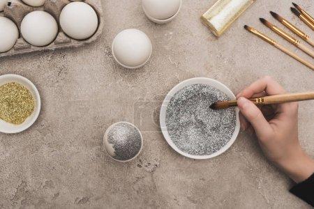 Foto de Vista cortada de la mujer decorando el huevo de pollo con brillo plateado en la superficie de hormigón gris. - Imagen libre de derechos