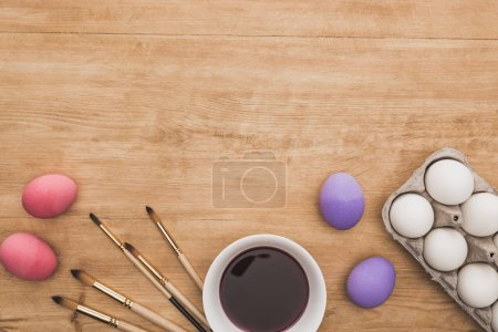Photo for Top view of watercolor purple paint in bowl near chicken eggs and paintbrushes on wooden table - Royalty Free Image