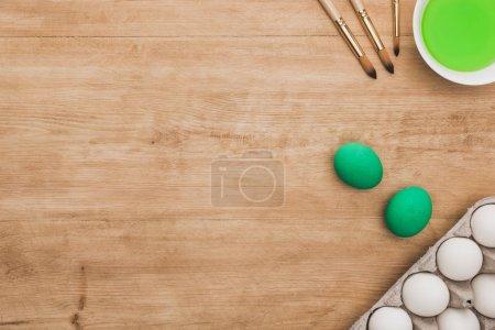 Photo pour Vue du dessus de la peinture à l'aquarelle verte dans un bol près des œufs de poulet et des pinceaux sur une table en bois - image libre de droit