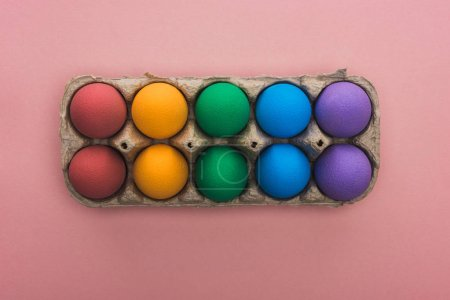 Photo for Top view of painted Easter eggs in cardboard box on pink background - Royalty Free Image