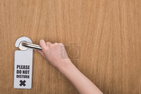 Photo for Cropped view of woman holding door handle with please do no disturb sign - Royalty Free Image