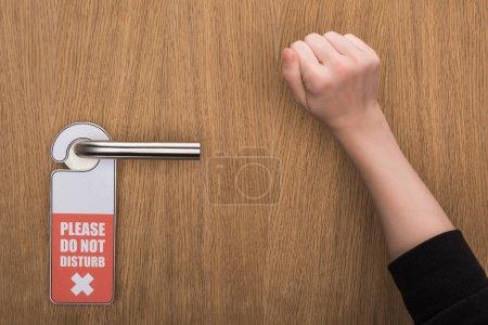 Photo pour Crochet vue de la femme frapper à la porte avec s'il vous plaît ne dérangez pas panneau - image libre de droit