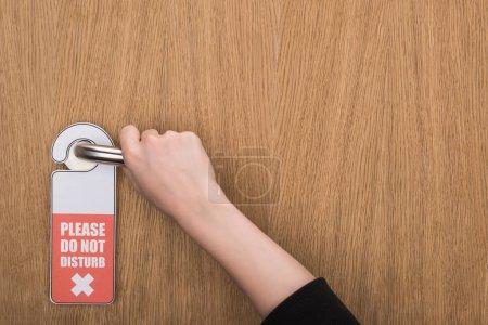 Photo pour Vue partielle de la femme tenant la poignée de porte avec s'il vous plaît ne dérangez pas le signe - image libre de droit