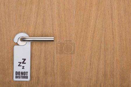 Photo pour Porte en bois de la chambre d'hôtel avec ne pas déranger le panneau sur la poignée - image libre de droit