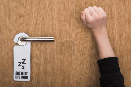 cropped view of woman knocking at door with do no disturb sign