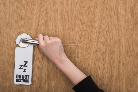 Photo for Partial view of woman holding door handle with do no disturb sign - Royalty Free Image