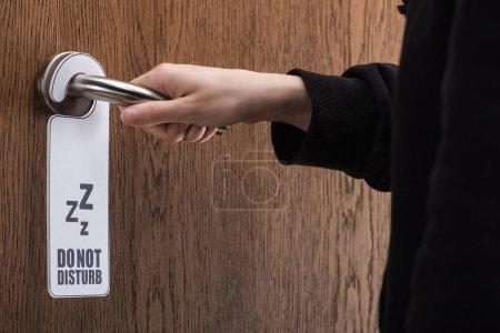 Photo pour Vue partielle de la femme tenant poignée de porte avec ne pas déranger signe - image libre de droit