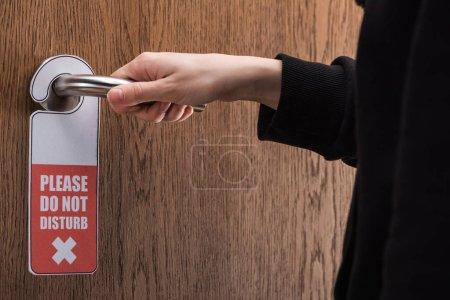 Photo pour Vue partielle de la femme tenant poignée de porte avec s'il vous plaît ne pas déranger signe - image libre de droit