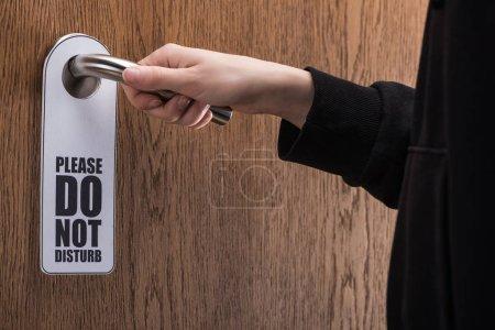 Photo pour Crochet de la femme tenant la poignée de la porte avec s'il vous plaît ne dérangez pas le panneau - image libre de droit