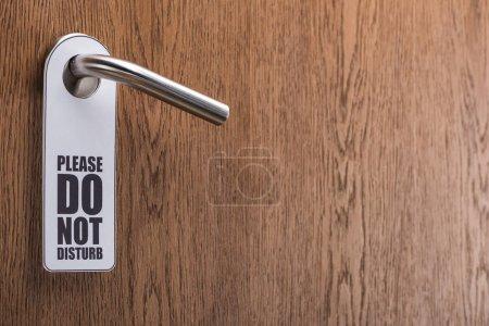 Photo pour La porte en bois de la chambre d'hôtel avec s'il vous plaît ne pas déranger le panneau sur la poignée - image libre de droit