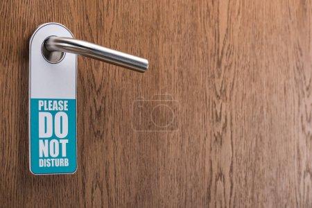 Photo pour Porte de chambre d'hôtel en bois avec s'il vous plaît ne pas déranger signe sur la poignée - image libre de droit