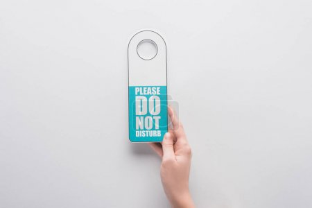 Photo for Cropped view of woman holding please do no disturb sign on white background - Royalty Free Image