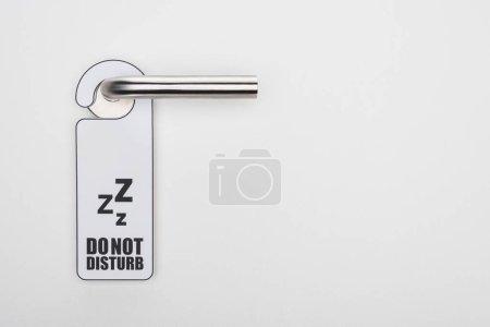 Photo pour Ne pas déranger le panneau sur la poignée sur fond blanc - image libre de droit