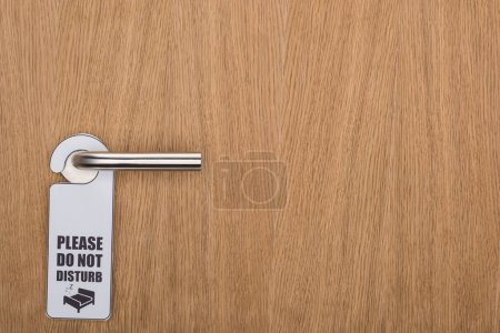 Photo for Wooden hotel room door with please do no disturb sign on handle - Royalty Free Image