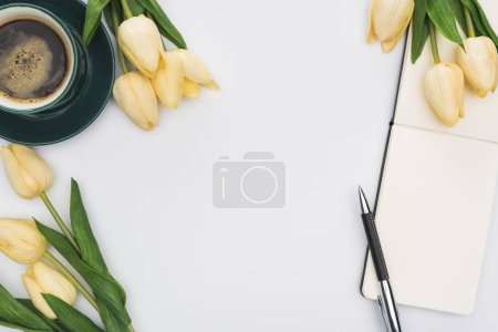 Photo for Top view of tulips, blank notebook with pen and fresh coffee isolated on white - Royalty Free Image