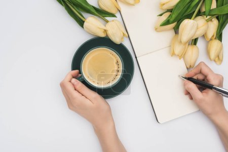 Photo for Cropped view of woman writing in blank notebook with pen near tulips and fresh coffee isolated on white - Royalty Free Image