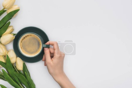Photo for Cropped view of woman holding cup of fresh coffee near tulips isolated on white - Royalty Free Image