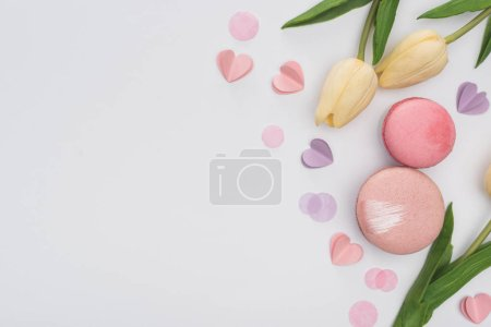 Photo for Top view of tulips, pink macarons and violet hearts isolated on white - Royalty Free Image