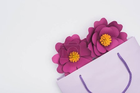 Photo for Top view of paper cut flowers in violet shopping bag isolated on white - Royalty Free Image
