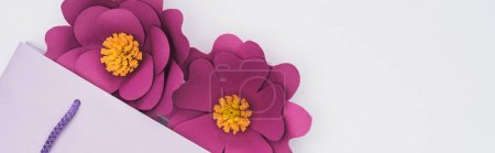 Photo for Top view of paper cut flowers in violet shopping bag isolated on white, panoramic shot - Royalty Free Image