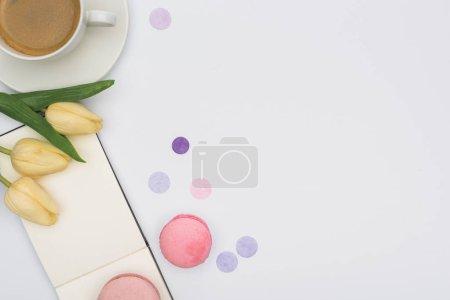 Photo pour Top view de tulipes, macarons, notebook vide et café isolé sur blanc - image libre de droit