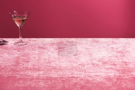 Photo for Alcohol drink in glass on velour pink cloth isolated on pink, girlish concept - Royalty Free Image