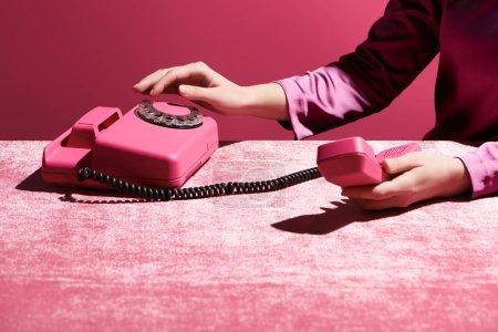 Photo pour Vue recadrée de la femme à l'aide d'un téléphone rétro sur tissu velours isolé sur rose, concept girlish - image libre de droit