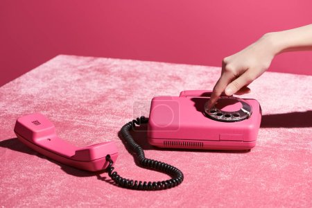 Photo for Cropped view of woman using retro phone on velour cloth isolated on pink, girlish concept - Royalty Free Image