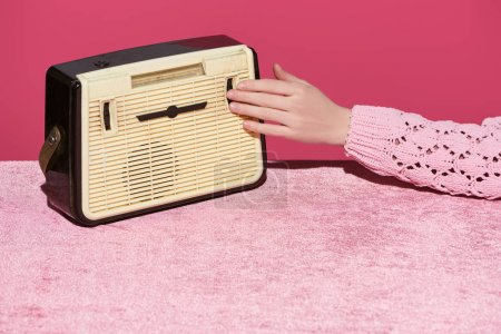Photo for Cropped view of woman with vintage radio on velour cloth isolated on pink, girlish concept - Royalty Free Image