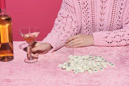 Photo pour Vue en coupe d'une femme tenant un verre de vin rose près de cubes avec des lettres sur du tissu de velours isolé sur un concept rose et filiforme - image libre de droit