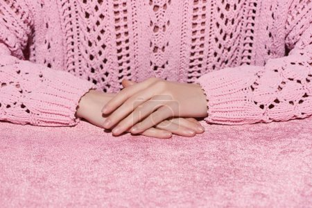 Photo for Cropped view of woman with clenched hands on velour pink cloth, girlish concept - Royalty Free Image